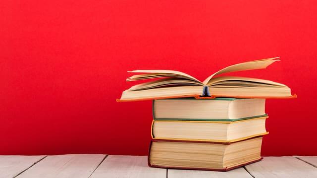 Vier Bücher sind auf einem Holzboden vor einer roten Wand aufeinandergestapelt.