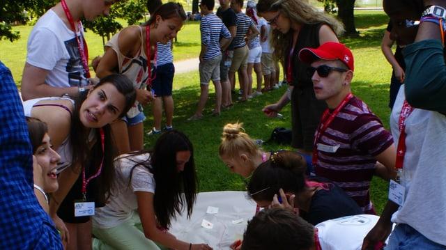 Eine Gruppe junger Erwachsener auf einer Wiese, zwischen sich ein weisses Tuch.