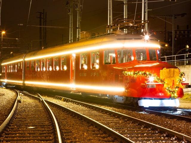 Ein roter, grell leuchtender und mit Weihnachtsschmuck dekorierter Zug.