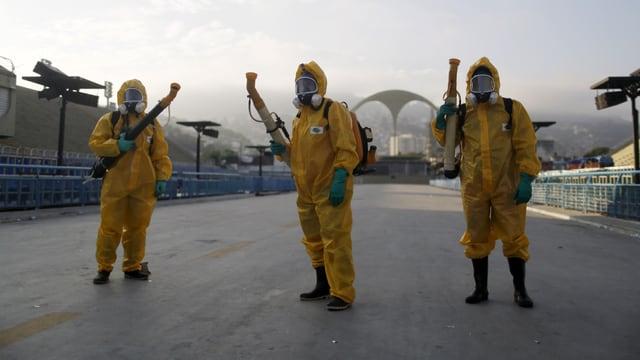 Drei Männer in gelben Schutzanzügen mit je einem Rohr zum Versprühen im Anschlag.
