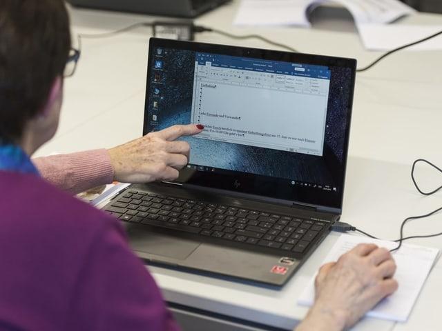 Blck über die Schultern einer Person, die einen Laptop bedient