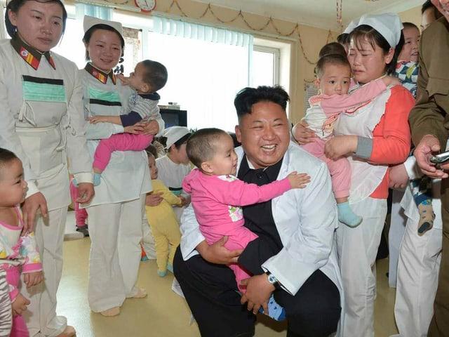 Diktator Kim Jong Un besucht ein Spital für Soldatenkinder und hält einen kleinen Bub auf den Knien.
