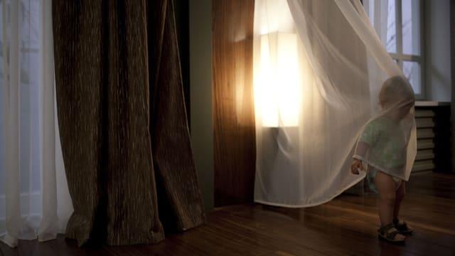 Ein kleines Kind umhüllt sich mit einem durchsichtigen Vorhang, wobei der Kopf und der Oberkörper bedeckt sind. Hinter dem Kind scheint die Sonne durch ein grosses Fenster.