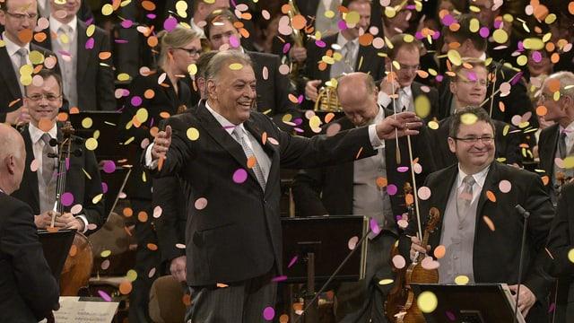 Orchestermusiker und Dirigent stehen, bunte Konfetti fallen herunter.