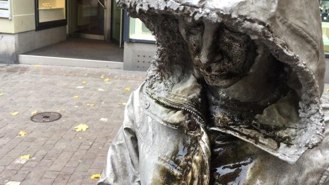 Skulptur einer Frau, die einen Kapuzenmantel trägt und weint.