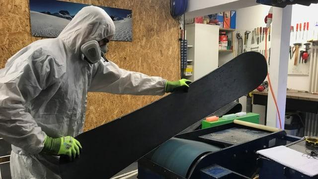 Ein Mann in weissem Overall und mit Atemschutz hält ein Snowboard auf eine Schleifmaschine