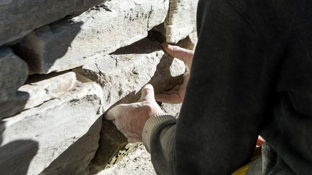 Grossaufnahme von den Händen eines Maurers bei der Arbeit.