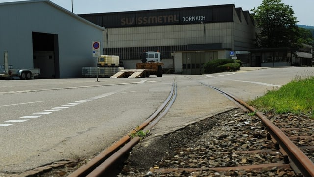 Blick auf das Swissmetal-Gebäude, aus der Froschperspektive. Zu sehen ist ein Gleis, das genau zum Gebäude hinführt. Links davon steht ein hellblaues Lagergebäude.
