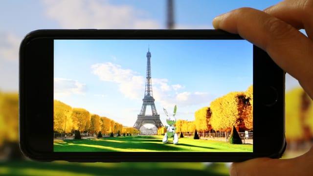 Ein Hand hält ein Smartphone. Darauf der Eiffelturm.