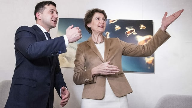 Der ukrainische Präsident und die Schweizer Bundesrätin zeigen in eine Richtung.
