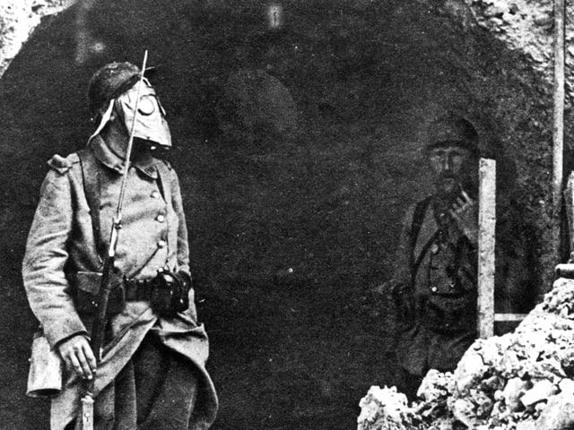 Zwei Männer stehen im Schutz eines Grabens. Der Mann links trägt eine Maske.