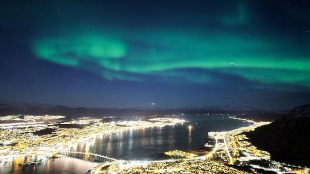 Grünes Polarlicht über dem Lichtermeer einer Stadt