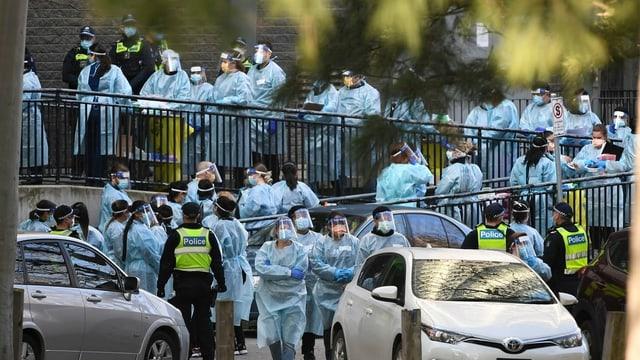 Gesundheitspersonal steht Warteschlange vor Häusern. Polizisten auch vor Ort.