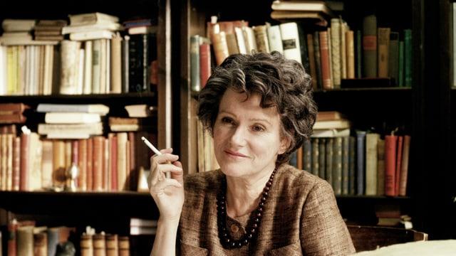 Eine Frau sitzt mit Zigarette in der Hand vor einem Bücherregal.