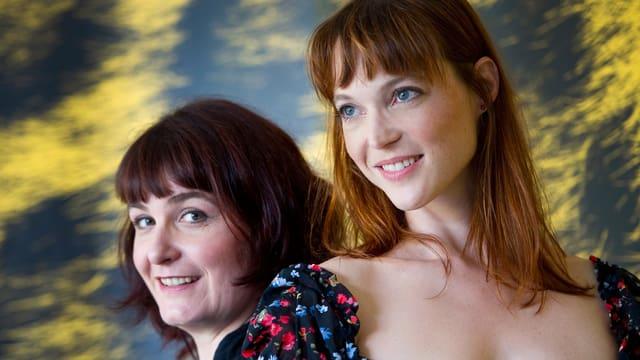 Zwei Frauen posieren vor der Kamera