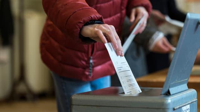 Symbolbild: Eine Person wirft ihren Abstimmungszettel in eine Urne.