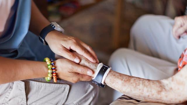 Hände einer betagten Person und einer jüngeren Frau, die ihre Pflegerin zu sein scheint.