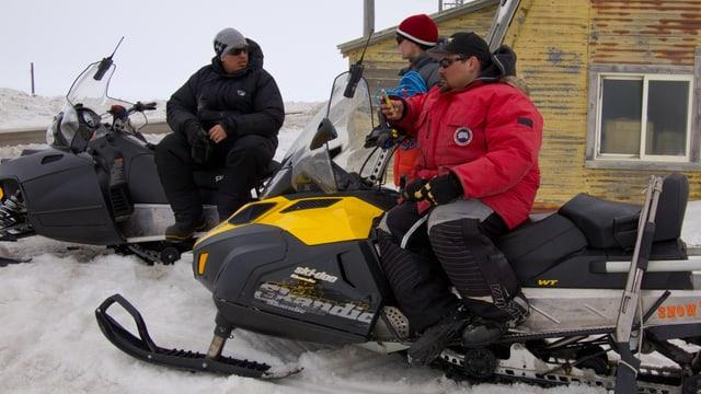 Ein Mann sitzt auf einem Schneemobil und schaut auf sein Handy.