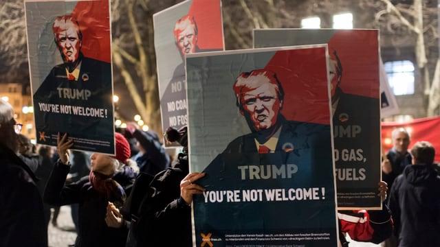 """Persunas cun placats cunter Trump cun l'inscripziun: """"Trump you're not welcome!"""