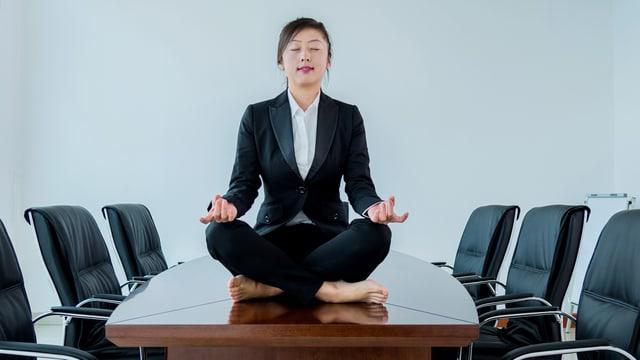 Eine Frau im Anzug sieht auf einem Sitzungtisch und meditiert.