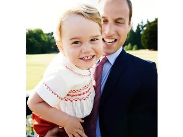 George sitzt bei seinem Vater auf dem Arm und grinst in die Kameras.