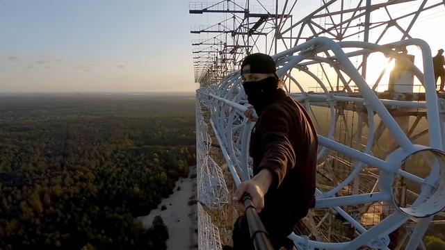 Ein junger Mann steht auf einer 200m hohen Metallkonstruktion und filmt sich selbst.