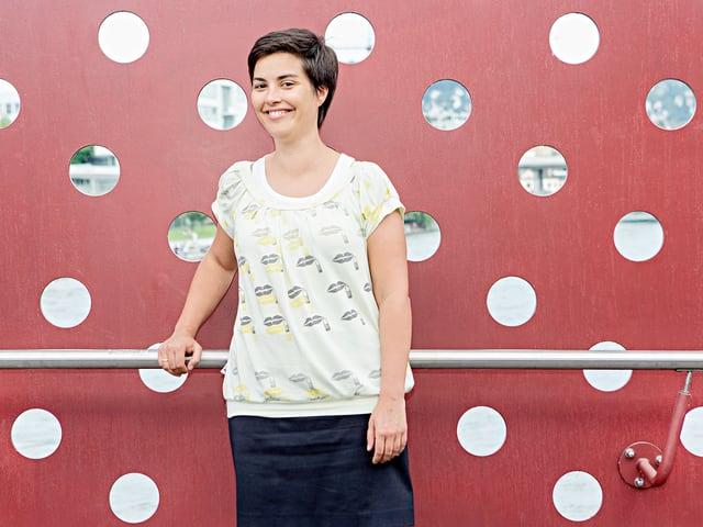Camille Roseau steht vor einer roten Wand mit Löchern.