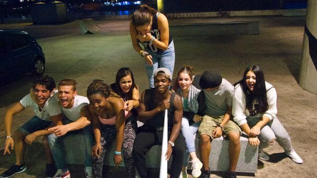 Eine Gruppe von jungen Männern und Frauen, die für den Fotographen posieren.