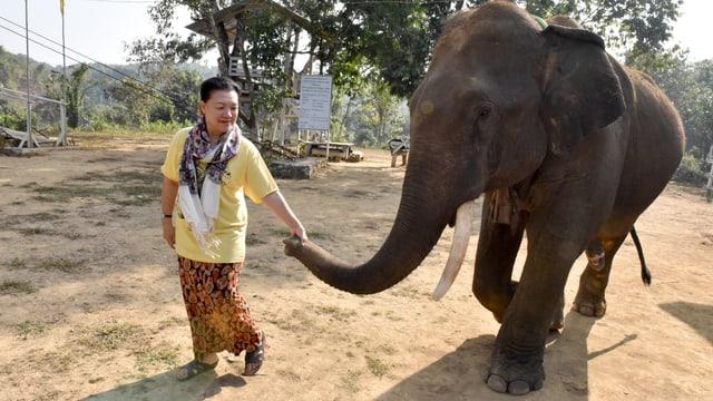Khyne U Mar hält den Rüssel eines Elefanten.
