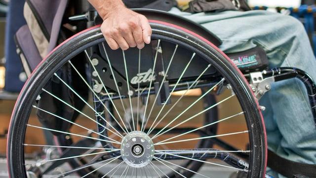 Das Rad eines Rollstuhls von der Seite.