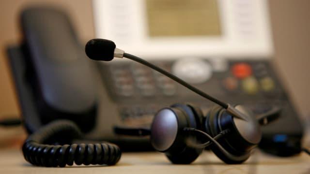 Ein Festnetztelefon, davor liegt ein Headset mit Kopfhörer und Mikrofon.