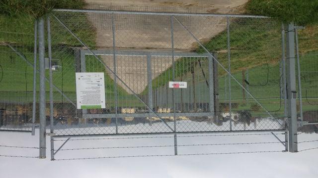 Eine grüne Wiese, davor zwei Eisentore mit Stacheldraht.