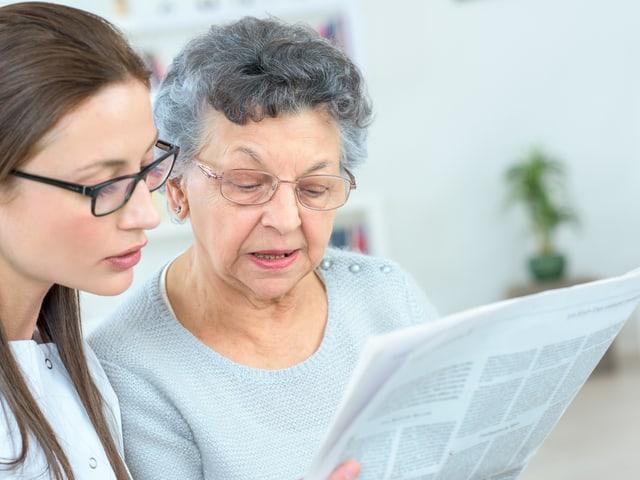 Junge Frau liest mit Seniorin einen Bericht durch.