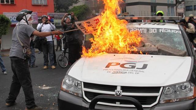 Vermummte neben einem brennenden Auto.