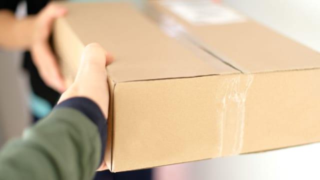 Ein Mann übergibt einer Frau ein Postpaket