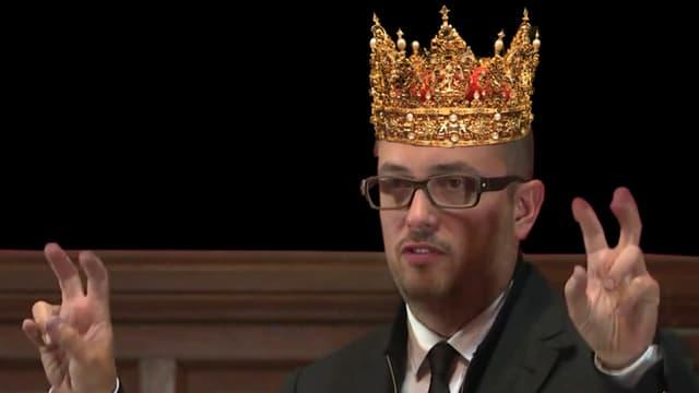 Das Bild zeigt eine Montage: Fabian Thylmann an einer Rede bei der Oxford Union, im Anzug und Krawatte, mit aufgesetzer Königskrone.