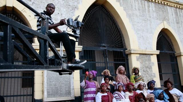 Ein Kameramann schwebt an einem Lenkarm über einer Gruppe Frauen.
