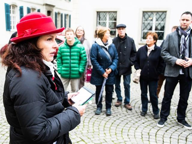 Die Führerin der Gruppe mit roten Hut. Sie steht neben den Bestatter-Fans.