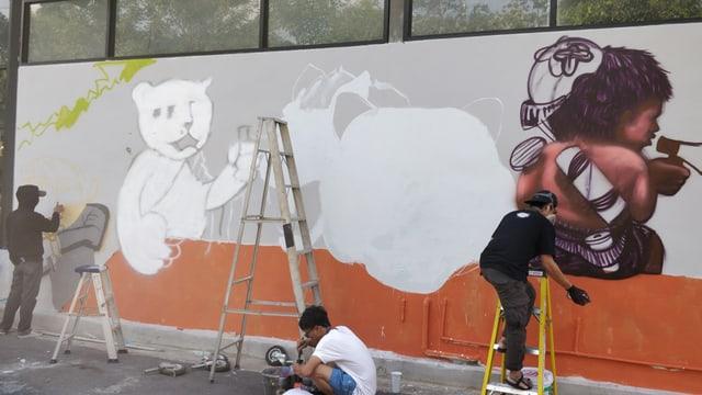 Malen von Graffiti an einer Hausmauer