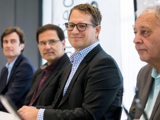Vier Männer anlässlich einer Medienkonferenz, man sieht sie von der Seite.