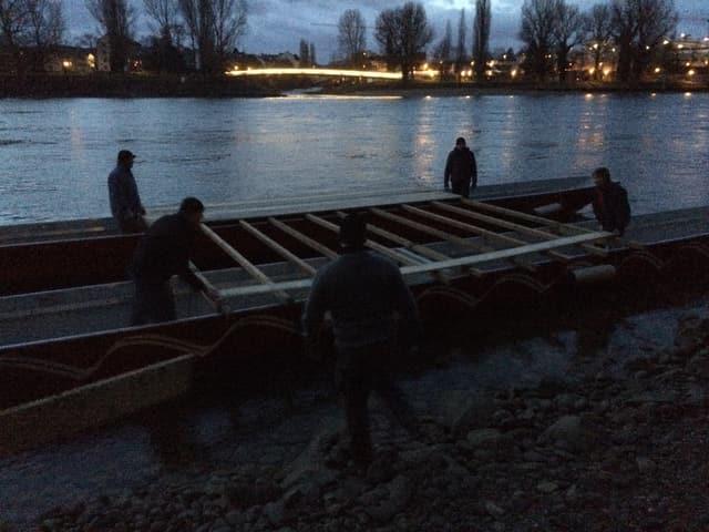 Männer tragen Holzlatten auf ein Boot.