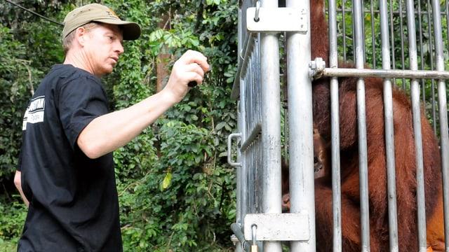 Ein Mann neben einem Affenkäfig