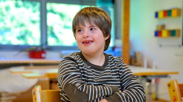 Behindertes Kind auf einem Hochstuhl in einem Schulzimmer.