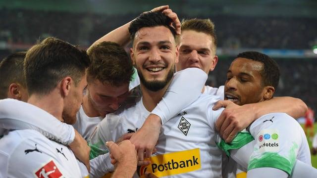 Ramy Bensebaini wird von seinen Teamkollegen umarmt.