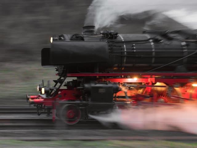 Eine schwarze Damplok fährt mit voller Kraft und dampft aus allen Rohren.