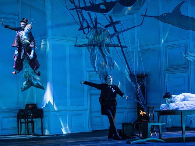 Bühne, auf welcher ein Schauspieler durch die Luft fliegt, ein weiterer auf der Bühne tanzt. Die Bühne ist in blaues Licht gehüllt und es wurde eine Art Unterwasserwelt kreiert.