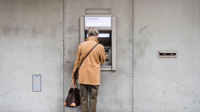 Eine Frau bezieht Geld an einem Bankomat.