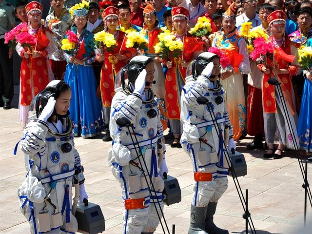 Die Astronauten salutieren – dahinter mehrere Frauen in traditionellen Gewändern mit Blumen.