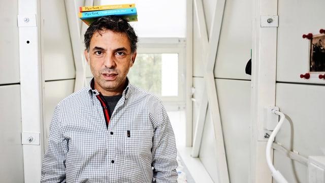 Etgart Keret in einem Raum mit weissen Wänden. Er trägt zwei Bücher auf dem Kopf.