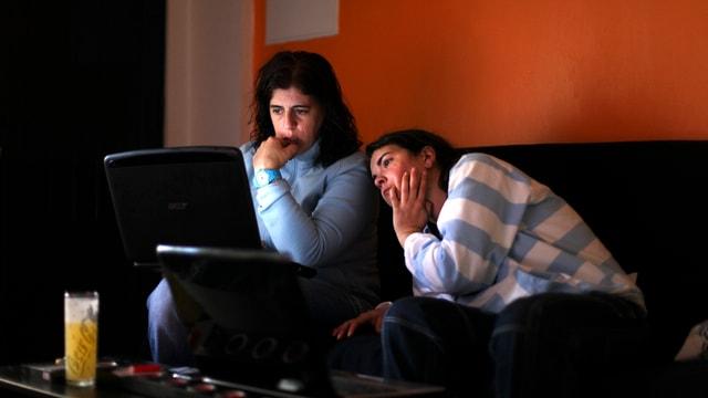 Zwei Frauen schauen gebannt auf den Bildschirm eine Laptops.